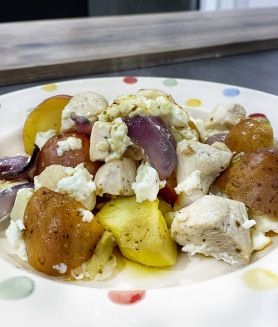 Plate of chicken, red potatoes, red onions, feta